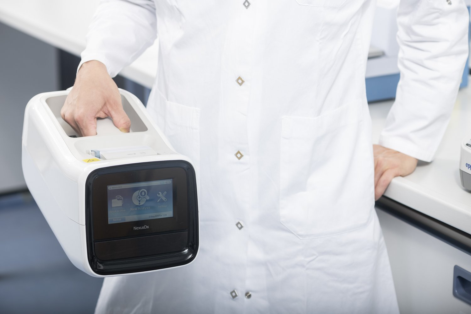 Close up of female research scientist holding the Nexus IB10 analyzer in laboratory setting.